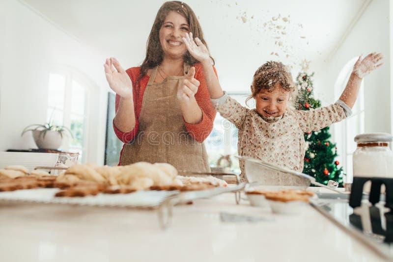 Madre e hija que se divierten mientras que hace las galletas de la Navidad fotografía de archivo