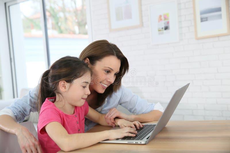Madre e hija que se divierten websurfing en un ordenador portátil imagen de archivo
