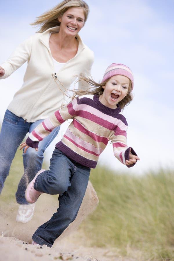 Madre e hija que se ejecutan en la sonrisa de la playa fotos de archivo libres de regalías