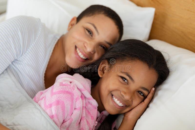 Madre e hija que se relajan junto en cama en dormitorio en casa foto de archivo