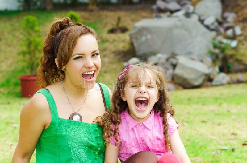 Madre e hija que se sientan afuera en parque imagenes de archivo
