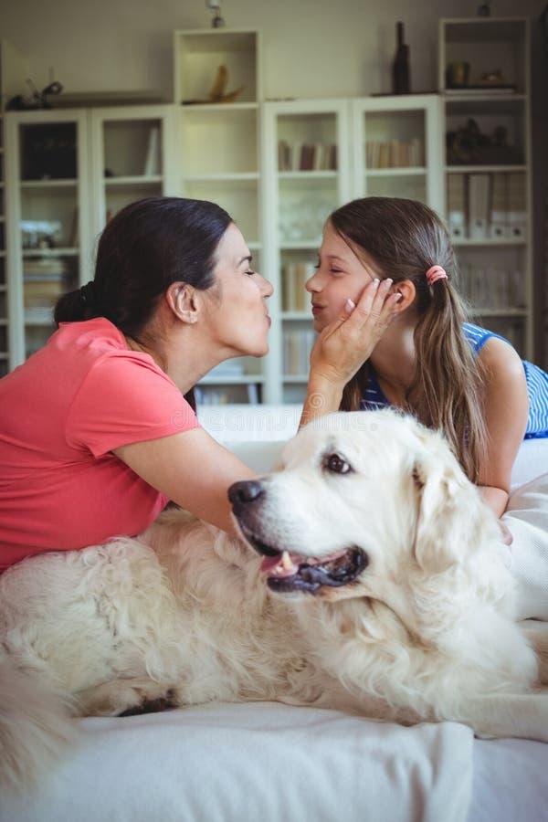 Madre e hija que se sientan con el perro casero en sala de estar foto de archivo
