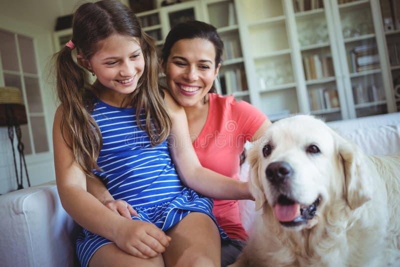 Madre e hija que se sientan con el perro casero en sala de estar imagenes de archivo