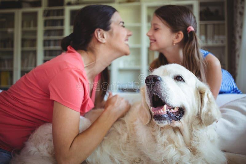 Madre e hija que se sientan con el perro casero en sala de estar imagen de archivo