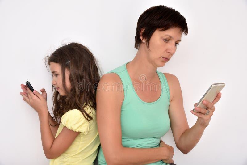 Madre e hija que se sientan de nuevo a la parte posterior con sus smartphones imagenes de archivo