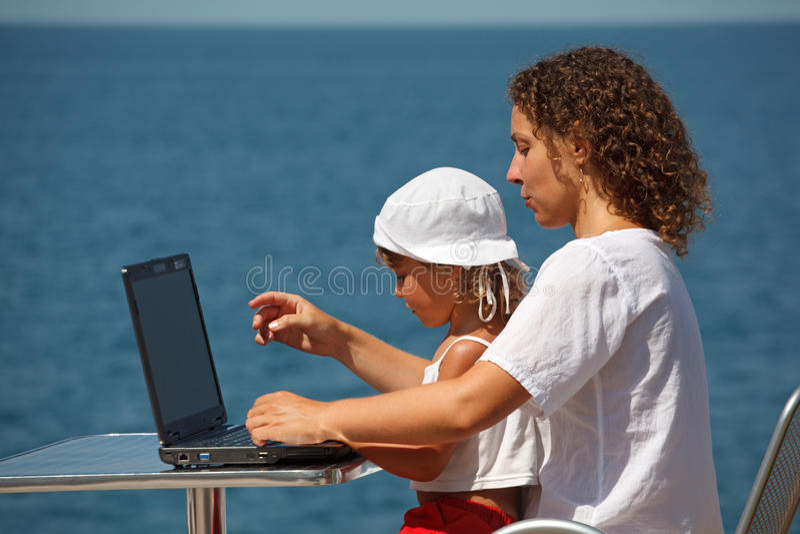 Madre e hija que se sientan en la computadora portátil foto de archivo
