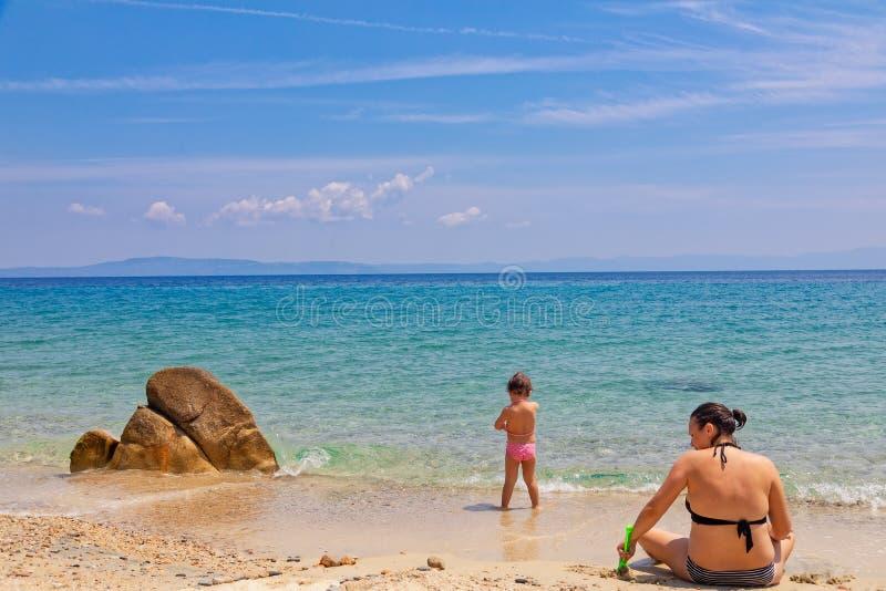 Madre e hija que se sientan en la playa, jugando con la arena el vacaciones de verano imagen de archivo