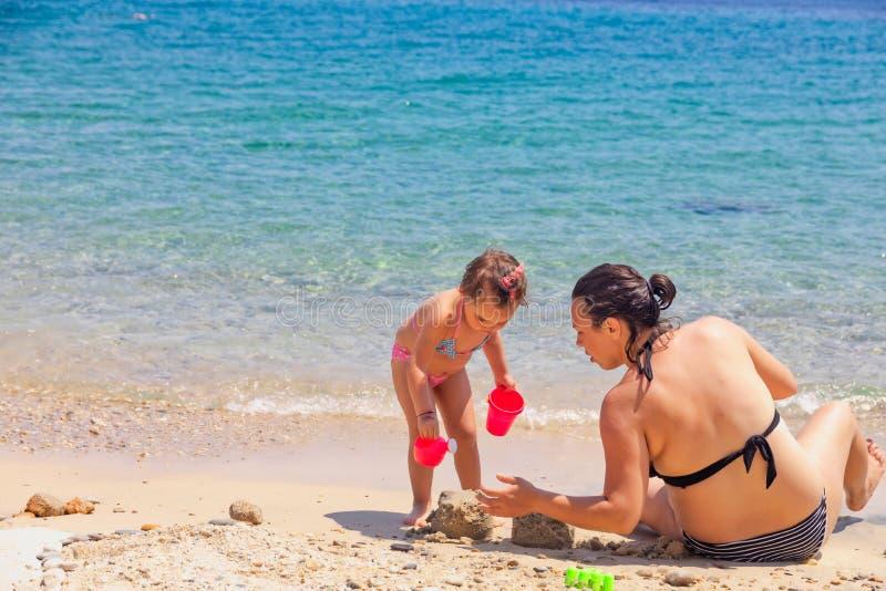 Madre e hija que se sientan en la playa, jugando con la arena el vacaciones de verano foto de archivo libre de regalías