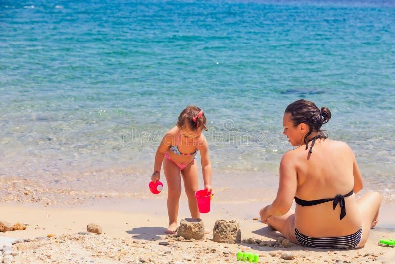 Madre e hija que se sientan en la playa, jugando con la arena el vacaciones de verano fotografía de archivo