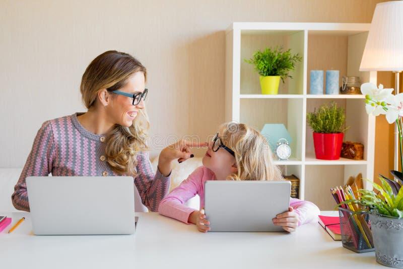 Madre e hija que se sientan en la tabla y que usan los ordenadores juntos fotos de archivo