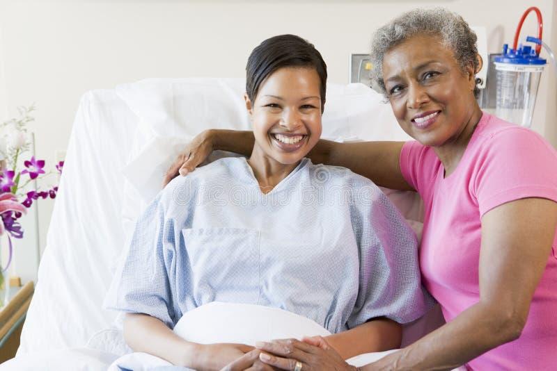 Madre e hija que sonríen en hospital fotografía de archivo