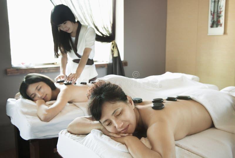 Madre e hija que tienen masaje de piedra caliente junto imagen de archivo libre de regalías