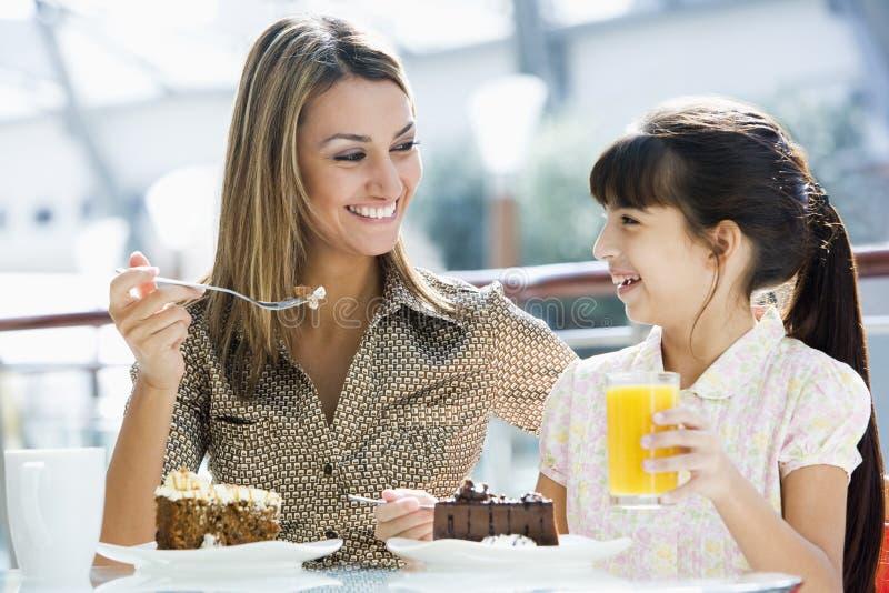 Madre e hija que tienen torta en el café imagenes de archivo