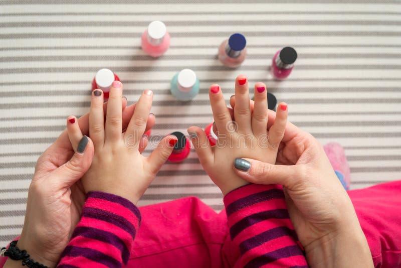 Madre e hija que tienen uñas de la pintura de la diversión, visión desde arriba foto de archivo libre de regalías
