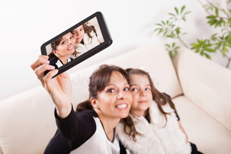 Madre e hija que toman los autorretratos con la tableta imagen de archivo
