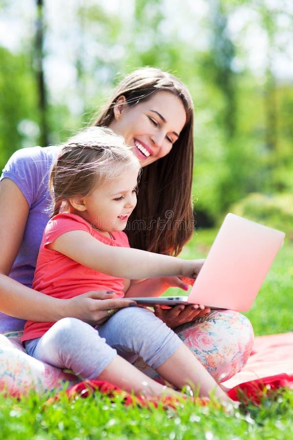 Madre e hija que usa el ordenador portátil al aire libre fotos de archivo libres de regalías