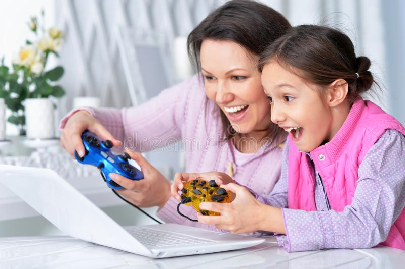 Madre e hija que usa el ordenador portátil junto que juega al juego foto de archivo