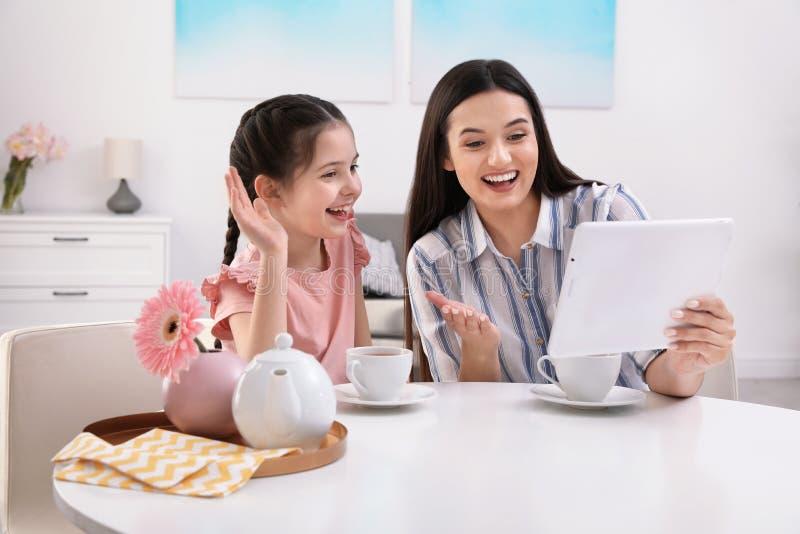 Madre e hija que usa la charla video en la tableta en la tabla fotos de archivo