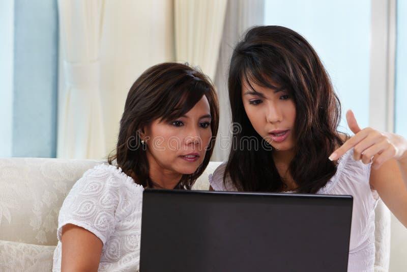 Madre e hija que usa la computadora portátil imágenes de archivo libres de regalías
