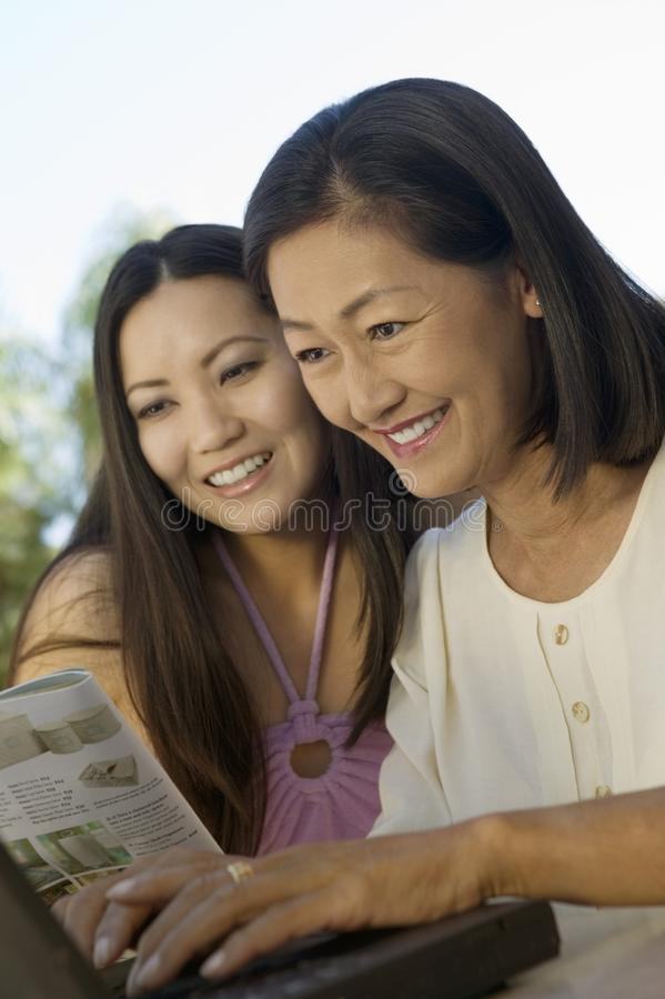 Madre e hija que usa la computadora portátil en el patio trasero imagenes de archivo