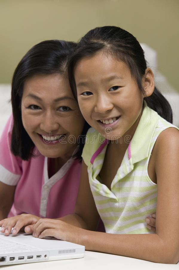 Madre e hija que usa la computadora portátil Togheter foto de archivo