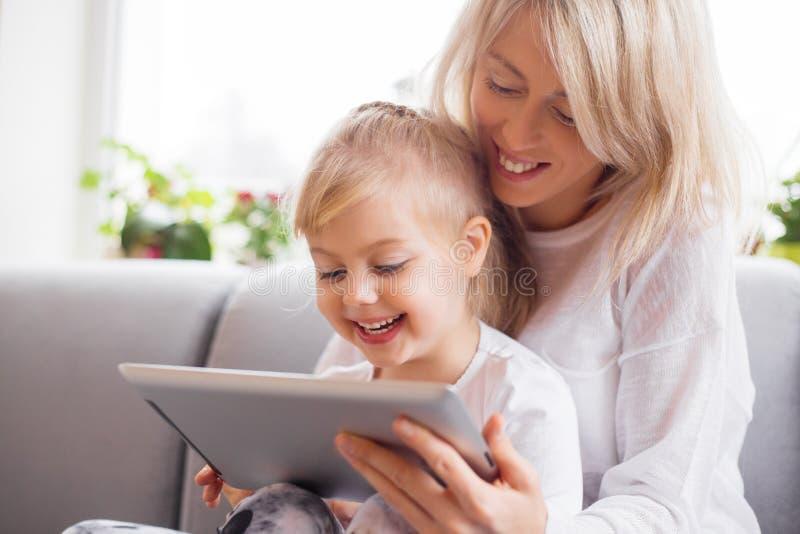 Madre e hija que usa la tableta junto imágenes de archivo libres de regalías