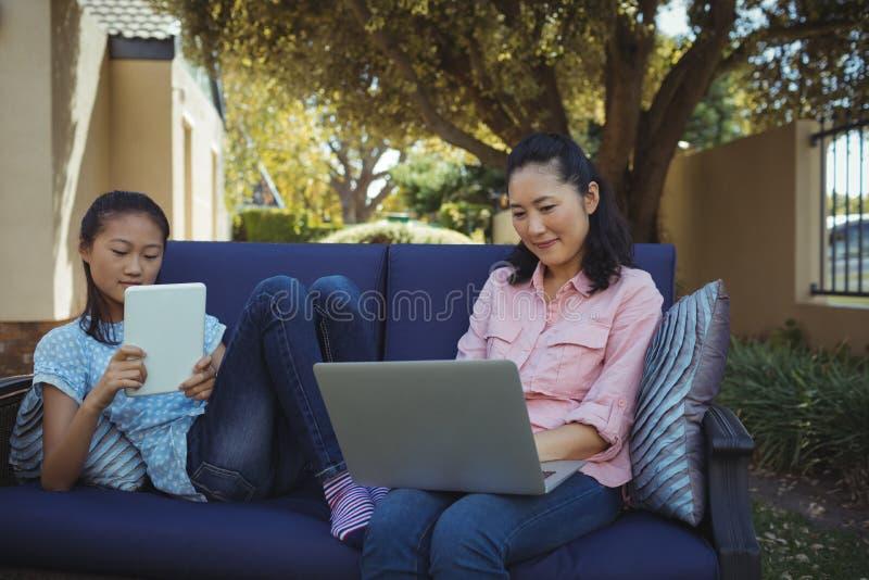Madre e hija que usa la tableta y el ordenador portátil digitales mientras que se relaja en el sofá foto de archivo