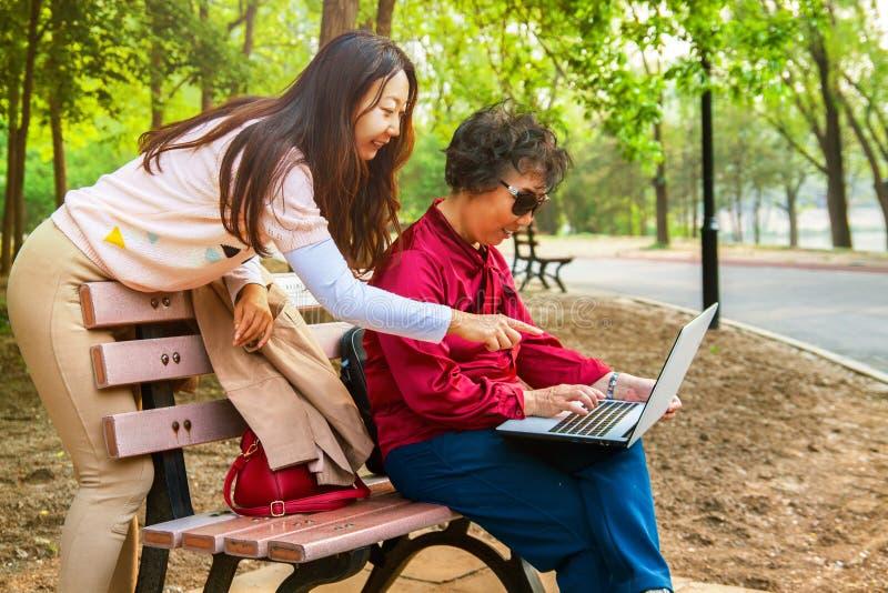 Madre e hija que usa un ordenador portátil en el jardín La hija enseña a una madre mayor a utilizar un ordenador imagen de archivo