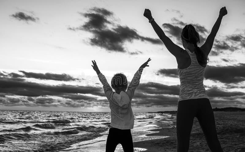 Madre e hija sanas en la costa en el júbilo de la puesta del sol foto de archivo