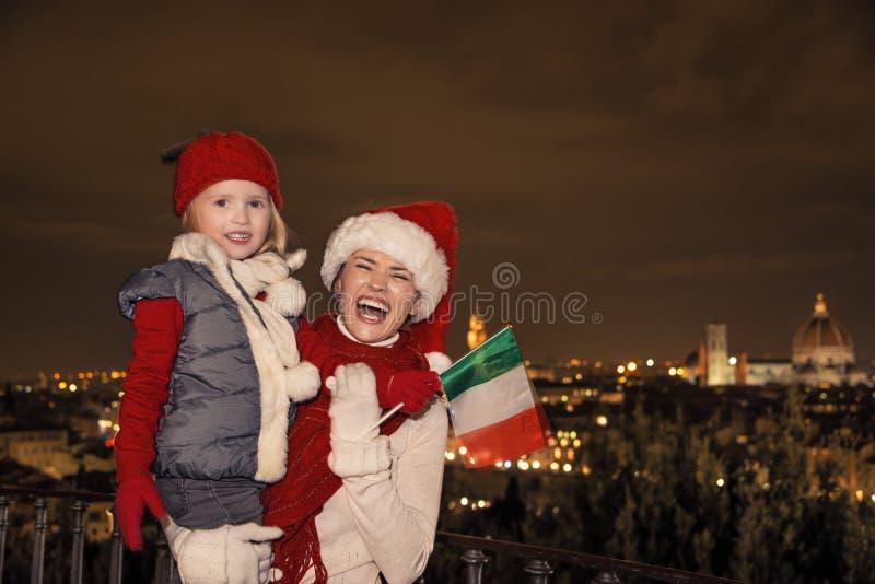 Madre e hija sonrientes en sombreros de la Navidad con la bandera italiana fotografía de archivo libre de regalías