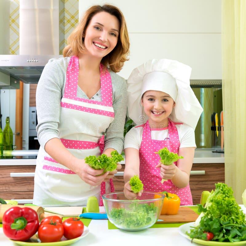 Madre e hija sonrientes que cocinan una ensalada foto de archivo