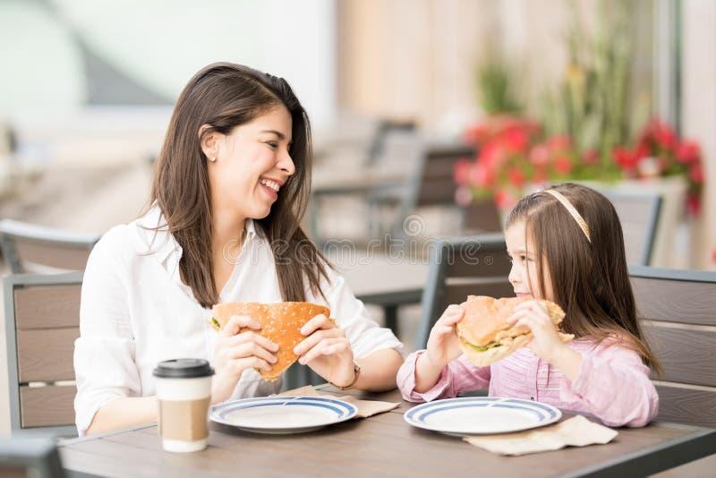 Madre e hija sonrientes que comen una hamburguesa imagen de archivo libre de regalías