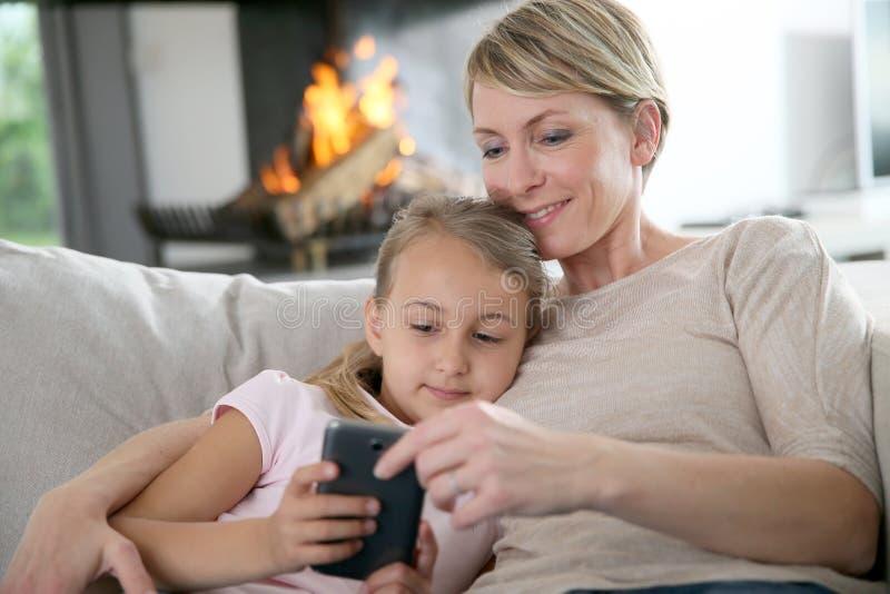 Madre e hija websurfing en smartphone imagen de archivo libre de regalías