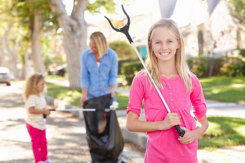 Madre e hijas que cogen la litera en calle suburbana imagenes de archivo