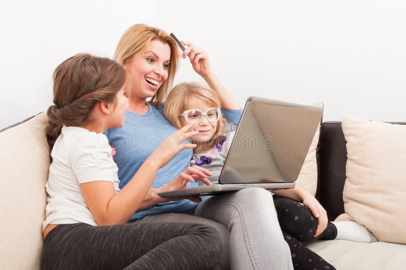 Madre e hijas que hacen compras en línea usando el ordenador portátil imagen de archivo