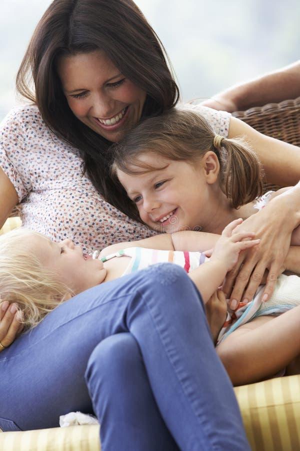 Madre e hijas que se relajan en el jardín Seat junto imagen de archivo libre de regalías