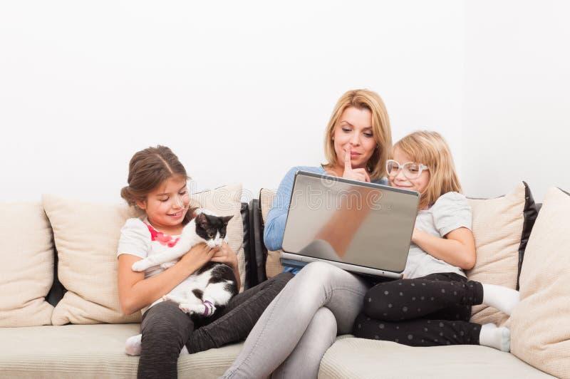 Madre e hijas que usan el ordenador portátil y jugando con el gato foto de archivo