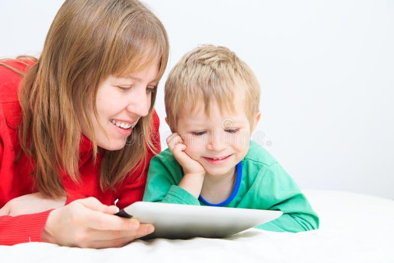 Madre e hijo con la almohadilla táctil en casa imagenes de archivo