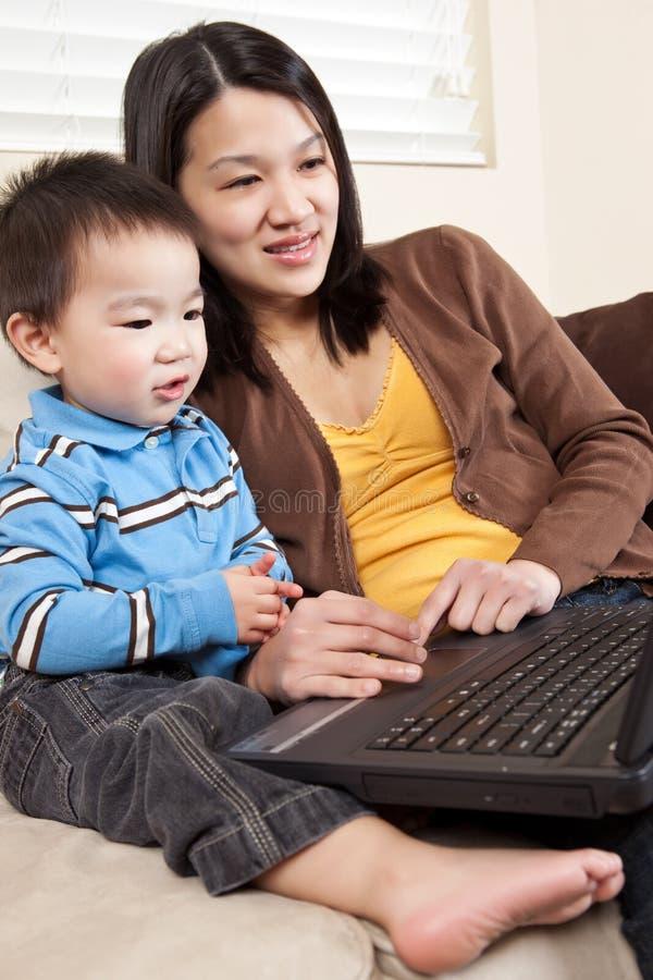 Madre e hijo con la computadora portátil foto de archivo libre de regalías