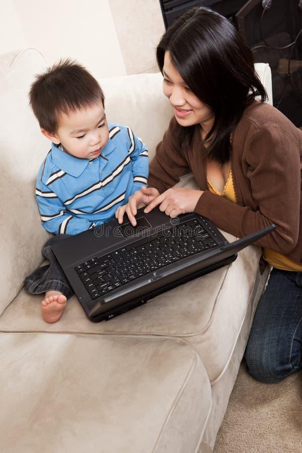 Madre e hijo con la computadora portátil fotos de archivo