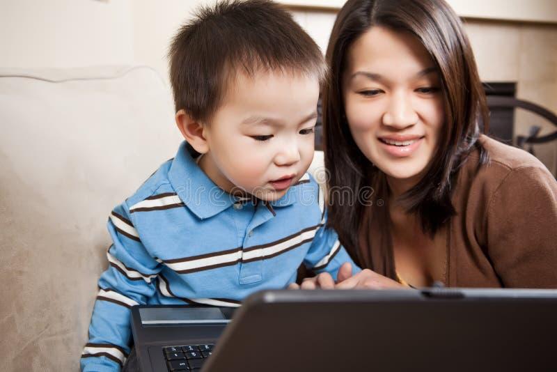 Madre e hijo con la computadora portátil fotografía de archivo
