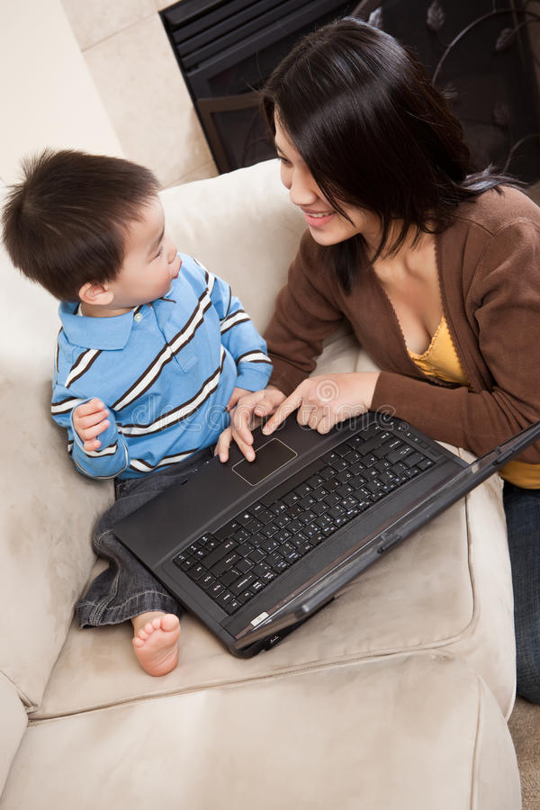 Madre e hijo con la computadora portátil foto de archivo