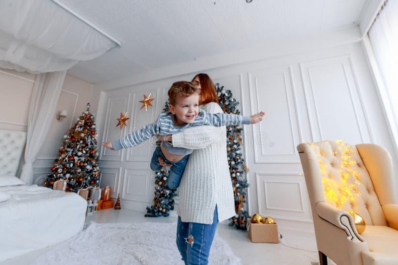 Madre e hijo delante de la Noche Vieja del árbol de navidad amor, felicidad y concepto de familia grande imágenes de archivo libres de regalías