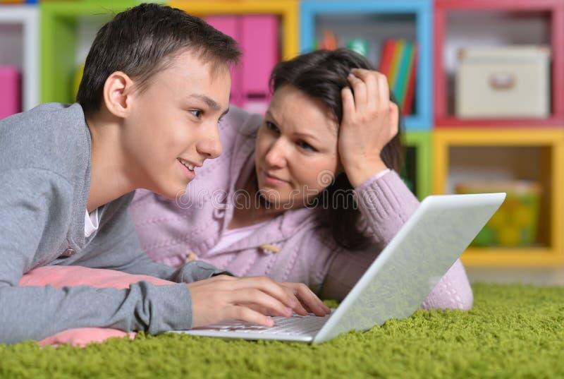 Madre e hijo emocionados con el ordenador port?til moderno foto de archivo