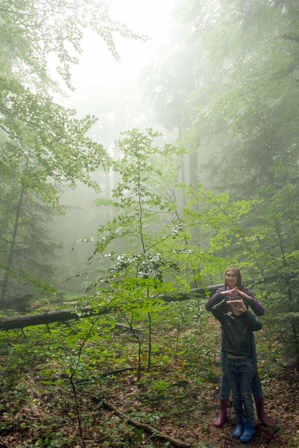 Madre e hijo en el bosque de niebla verde místico fotografía de archivo