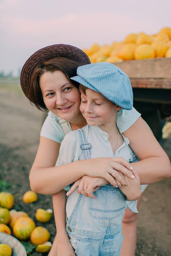 Madre e hijo en el carro con los melones foto de archivo