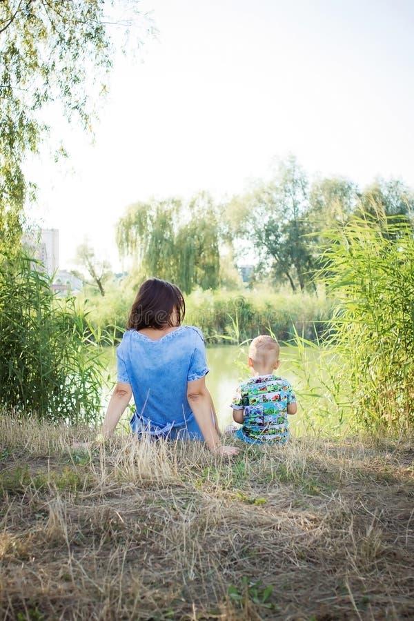Madre e hijo en la orilla del río imagen de archivo