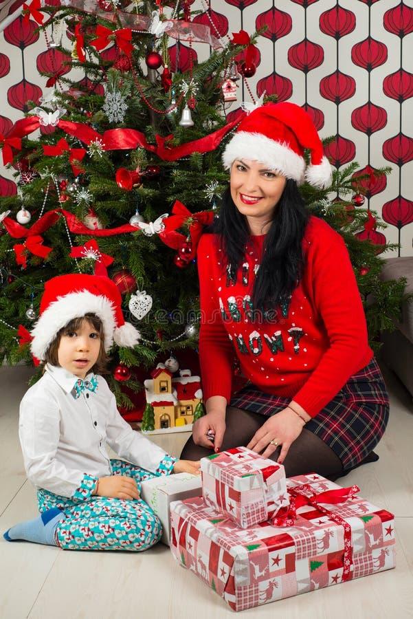 Madre e hijo felices con el árbol de navidad fotografía de archivo libre de regalías