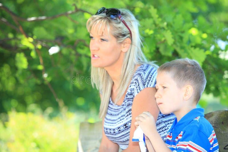 Madre e hijo felices de la familia en banco en parque imágenes de archivo libres de regalías