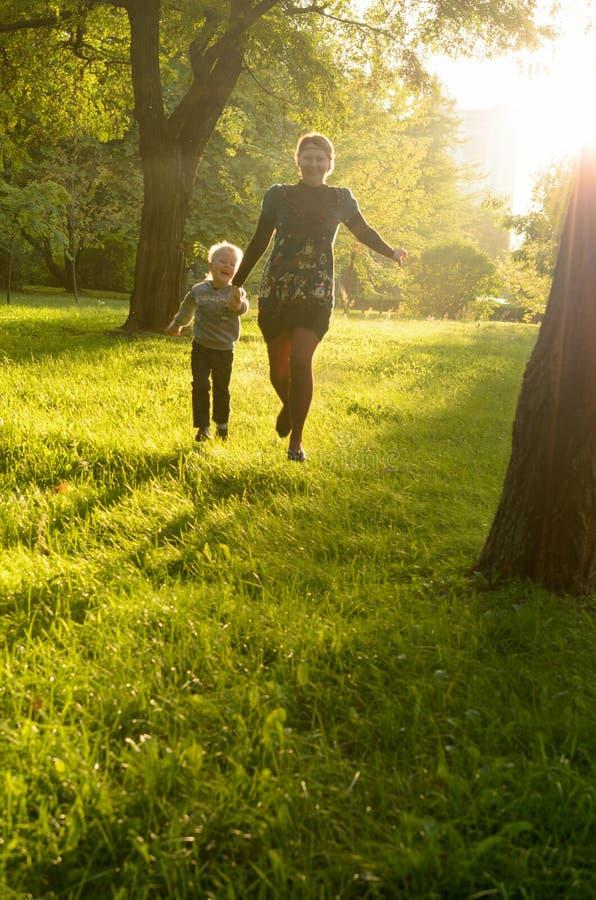 Madre e hijo joven que corren feliz a través de foto de archivo libre de regalías